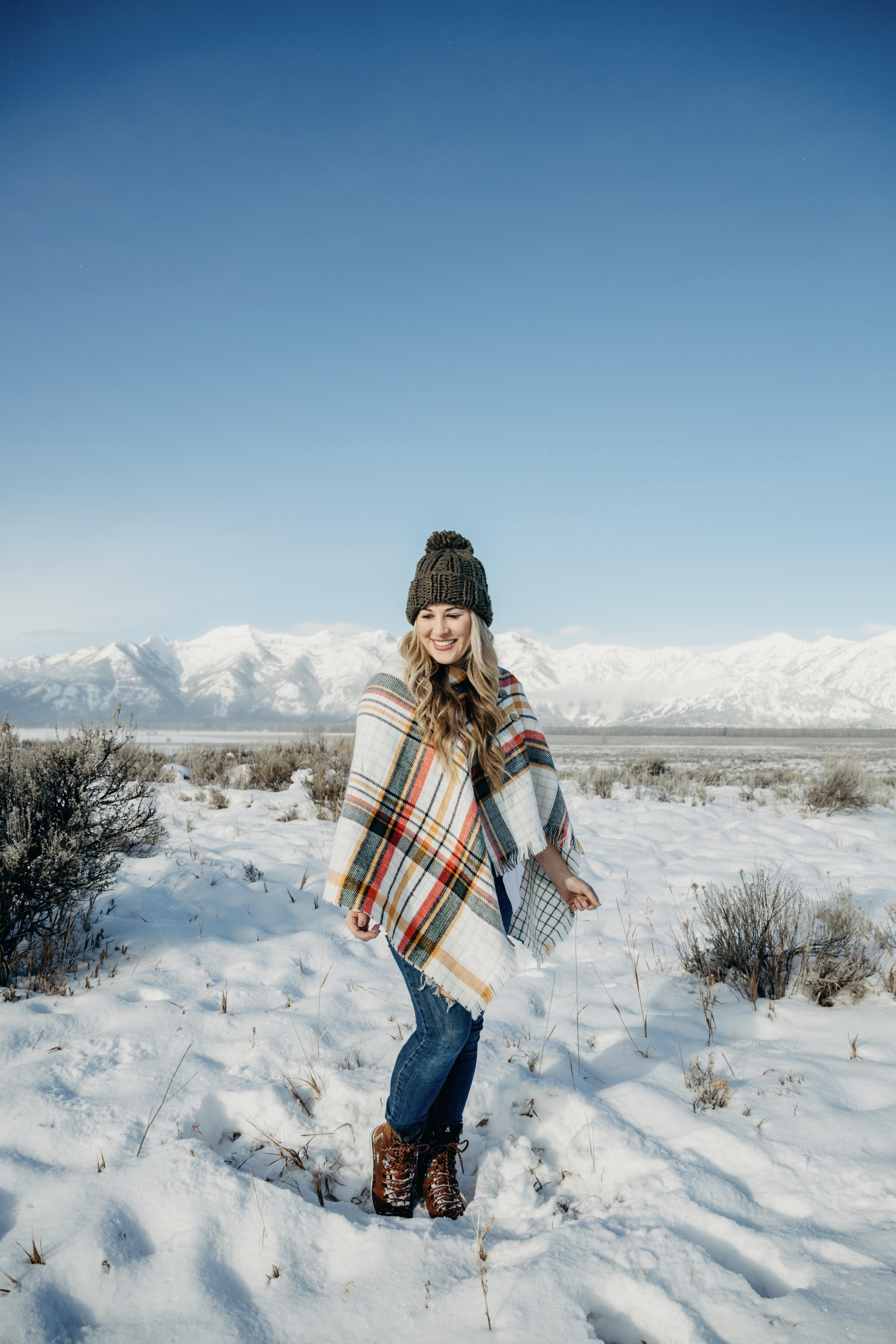 Cold Weather essentials featured by top US fashion blog, Walking in Memphis in High Heels: image of a woman wearing aGrace & Lace plaid poncho, Free People skinny jeans, Grace & Lace pom beanie, and KAMIK hiking boots