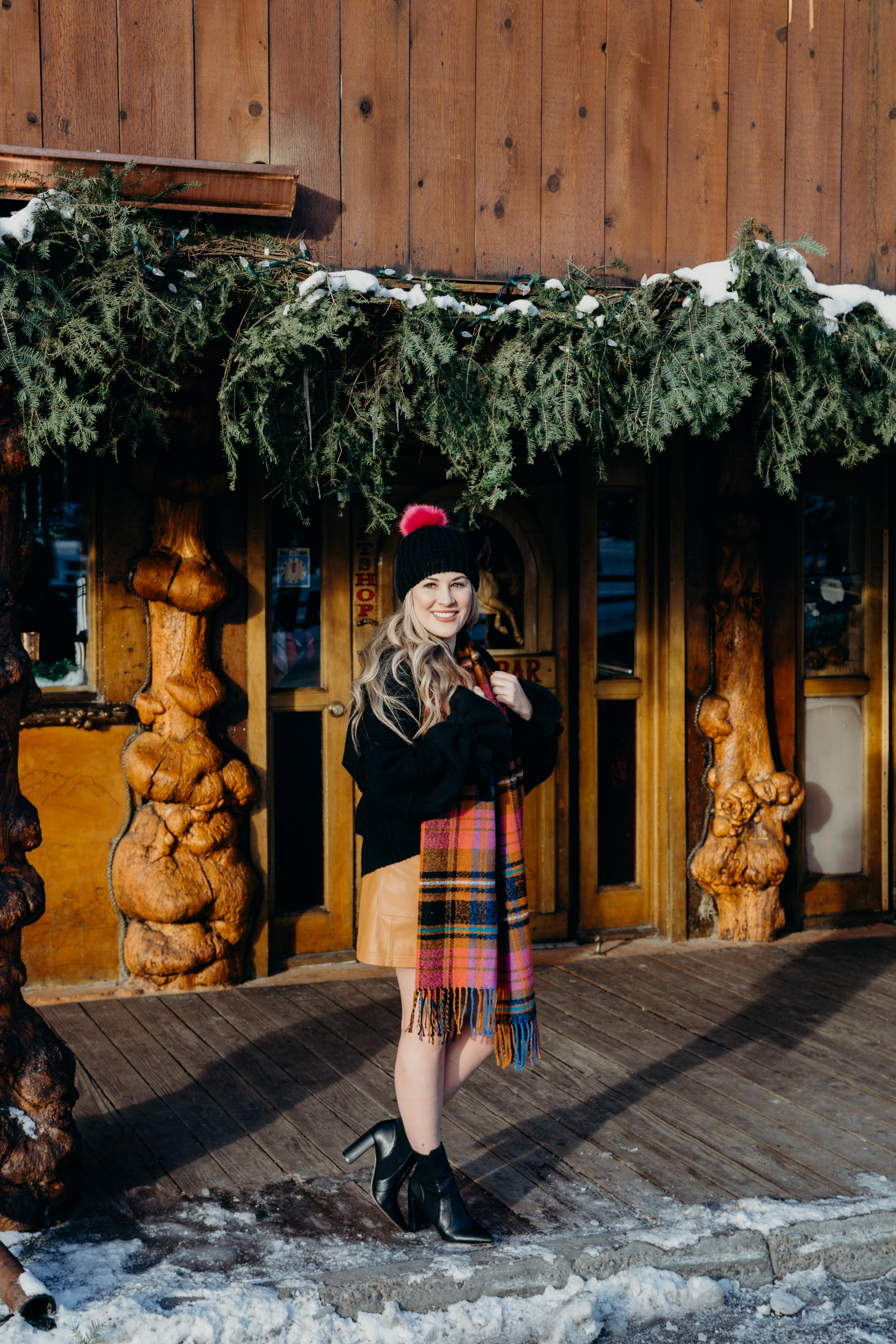 Christmas party look featured by top US fashion blog, Walking in Memphis in High Heels: image of a woman wearing a black Oracle sweater, Free People faux leather mini skirt, hot pink pom pom beanie, ASOS check scarf and Sole Society sock booties