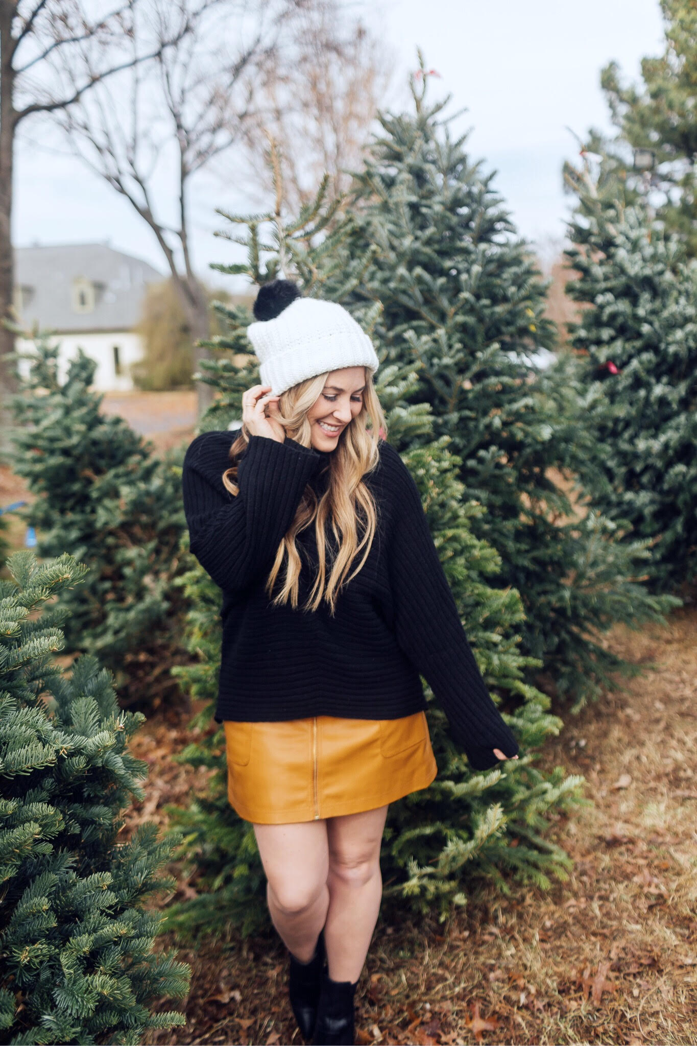 Winter accessories featured by top US fashion blog, Walking in Memphis in High Heels: image of a blonde woman walking in a Christmas tree farm wearing a Free People mini skirt, Melroseand Market sweater, Rebecca Minkoff pompom beanie, Sole Society Sock Bootie