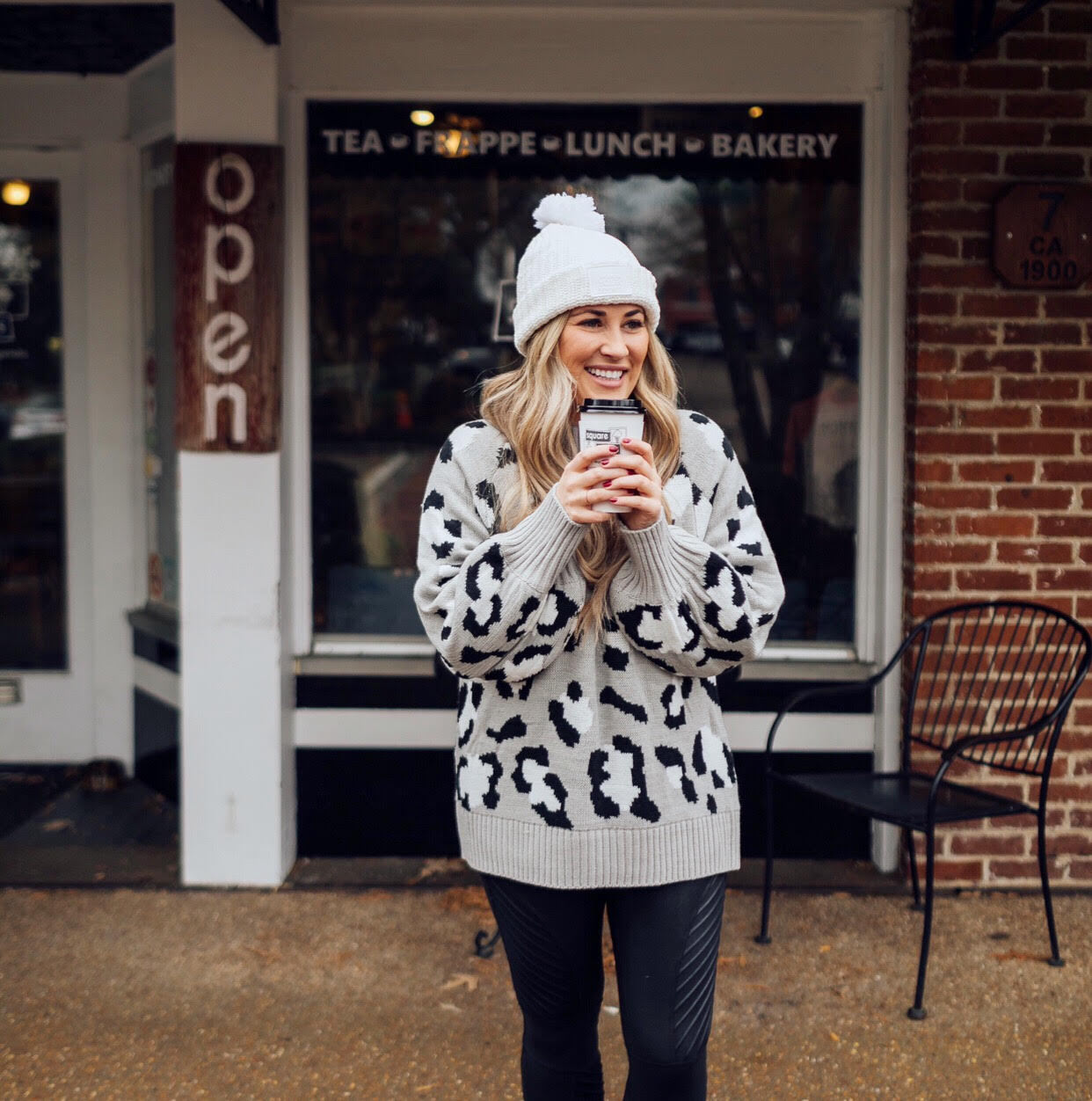 Casual winter wear styled by top US fashion blog, Walking in Memphis in High Heels: image of a woman wearing SPANX faux leather leggings, Pink Lily leopard print sweater, Adidas pink sneakers and faux fur double pom beanie hat