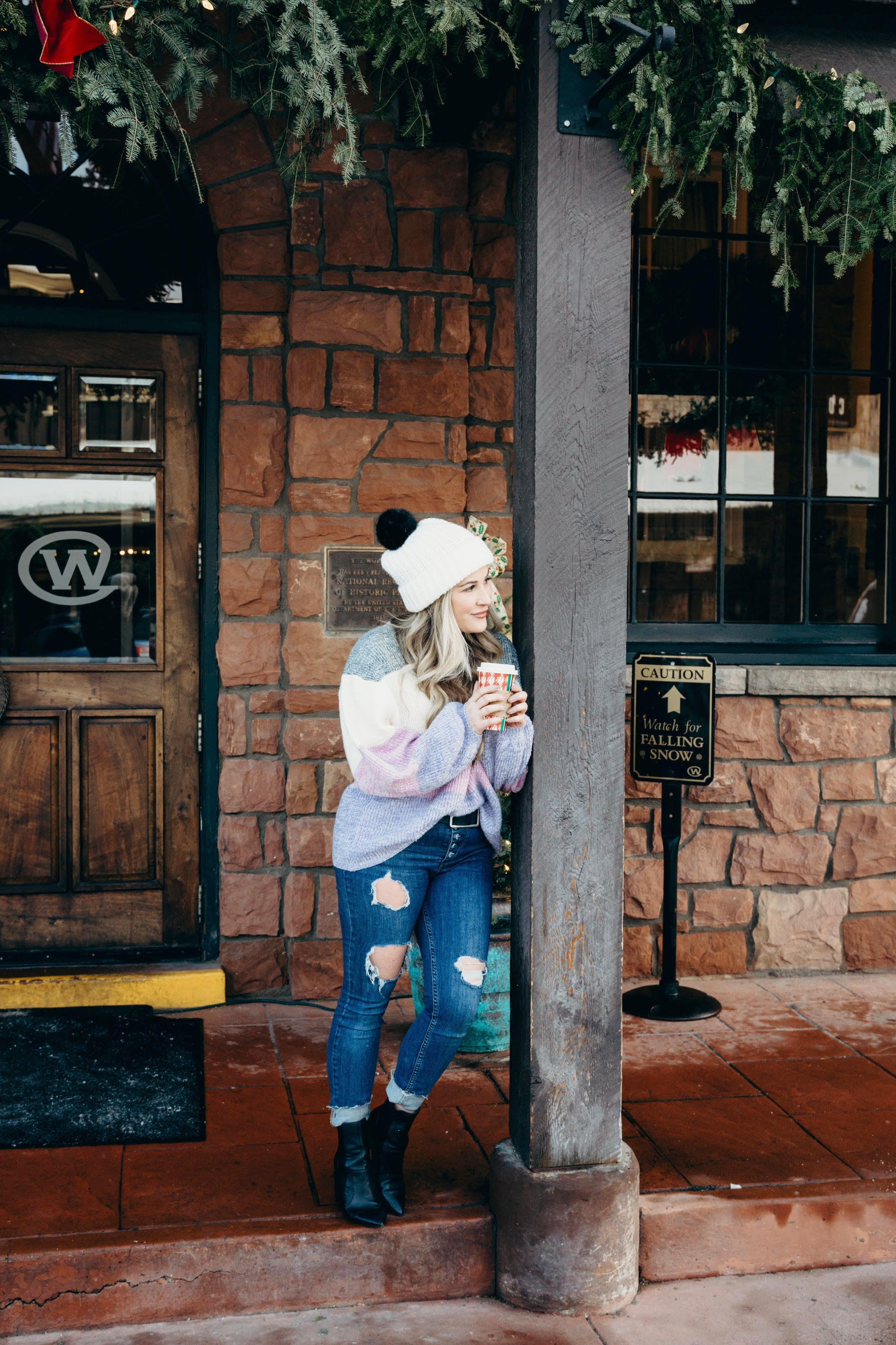 Pink Lily striped sweater styled by top US fashion blog, Walking in Memphis in High Heels: image of a woman wearing a Pink Lily striped sweater, Free People skinny jeans, Double faux fur pom pom beanie and Sole Society sole booties