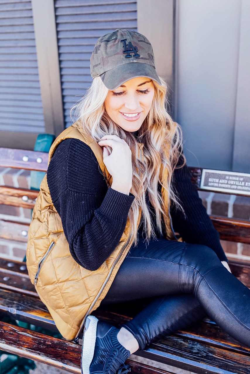 Gold Puffer Vest styled by top US fashion blog, Walking in Memphis in High Heels: image of a woman wearing a Patagonia gold puffer vest, SPANX faux leather leggings, Target tunic sweater, Adidas sneakers, and a LA Dodgers camouflage baseball cap.