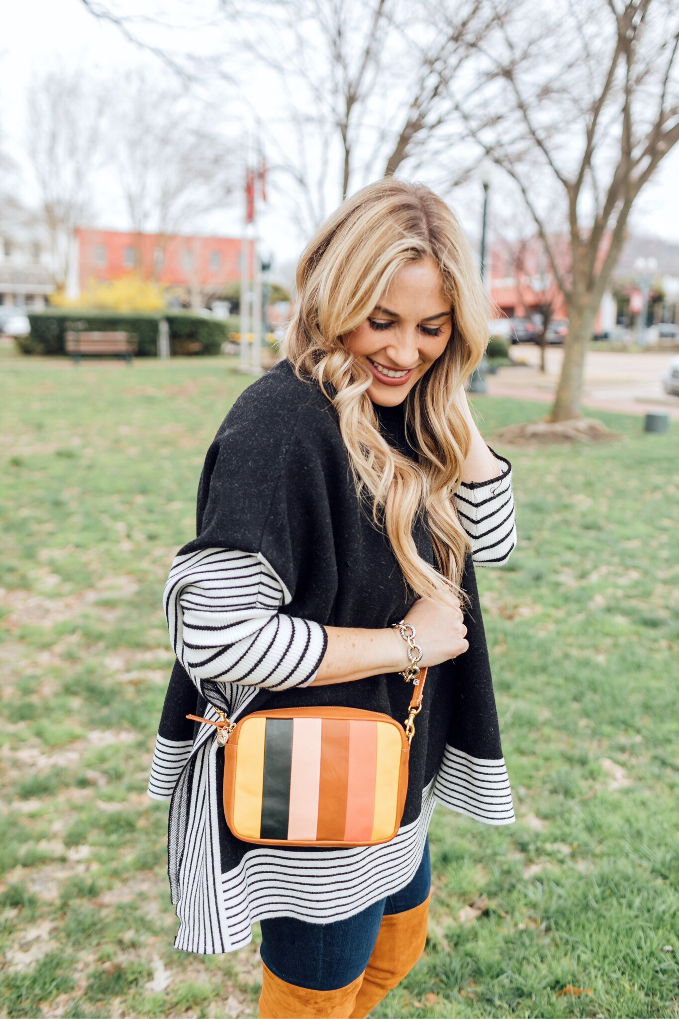 Colorful outfit featured by top US fashion blog, Walking in Memphis in High Heels: image of a woman wearing a Good American skinny jeans, a SheIn striped poncho jumper, Goodnight Macaroons suede over the knee boots and a Steve Madden crossbody bag