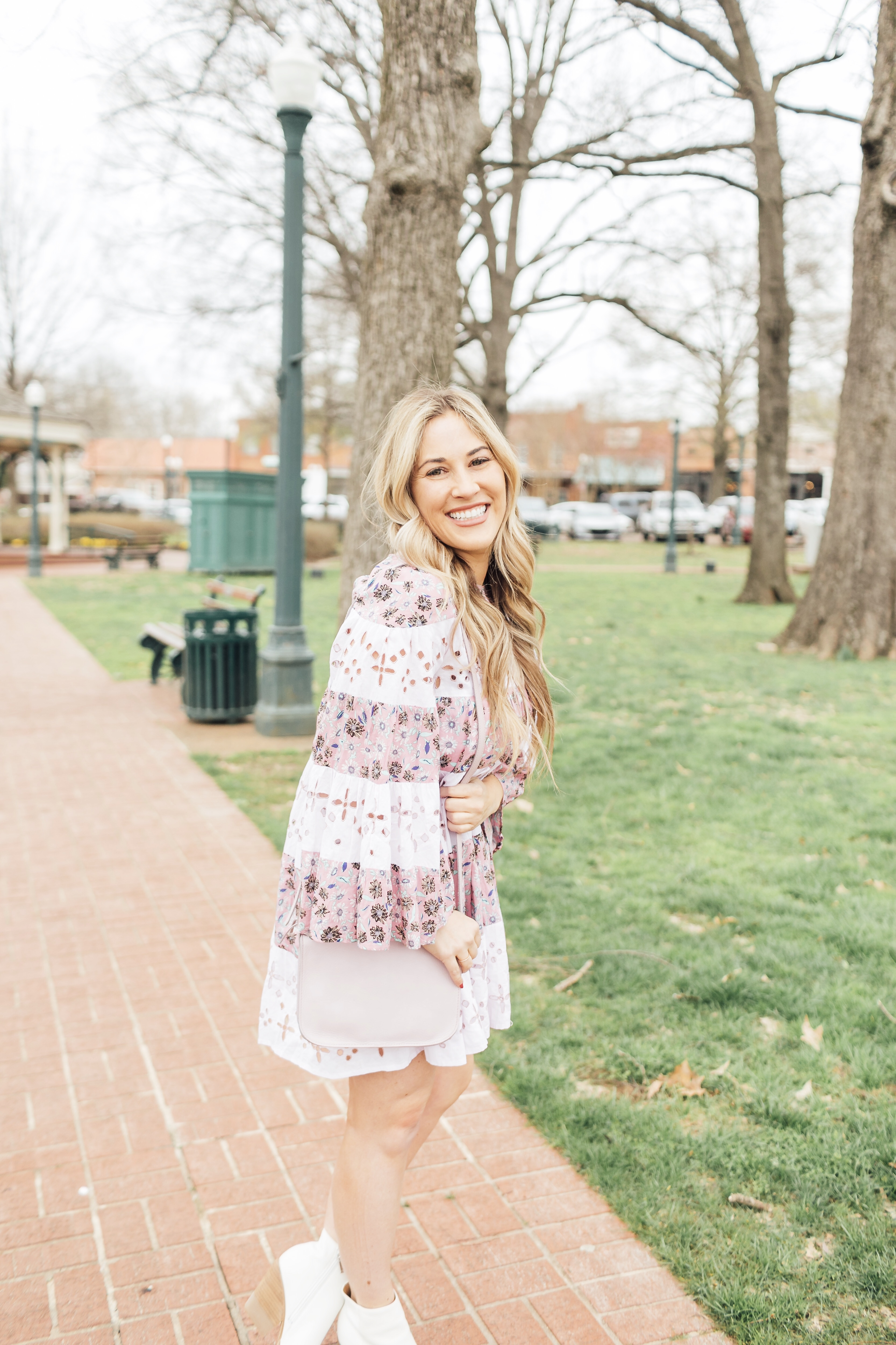 Spring style ideas featured by top US fashion blog, Walking in Memphis in High Heels: image of a woman wearing a Free People floral dress, Marc Fisher leather booties and a pink Madewell crossbody bag.