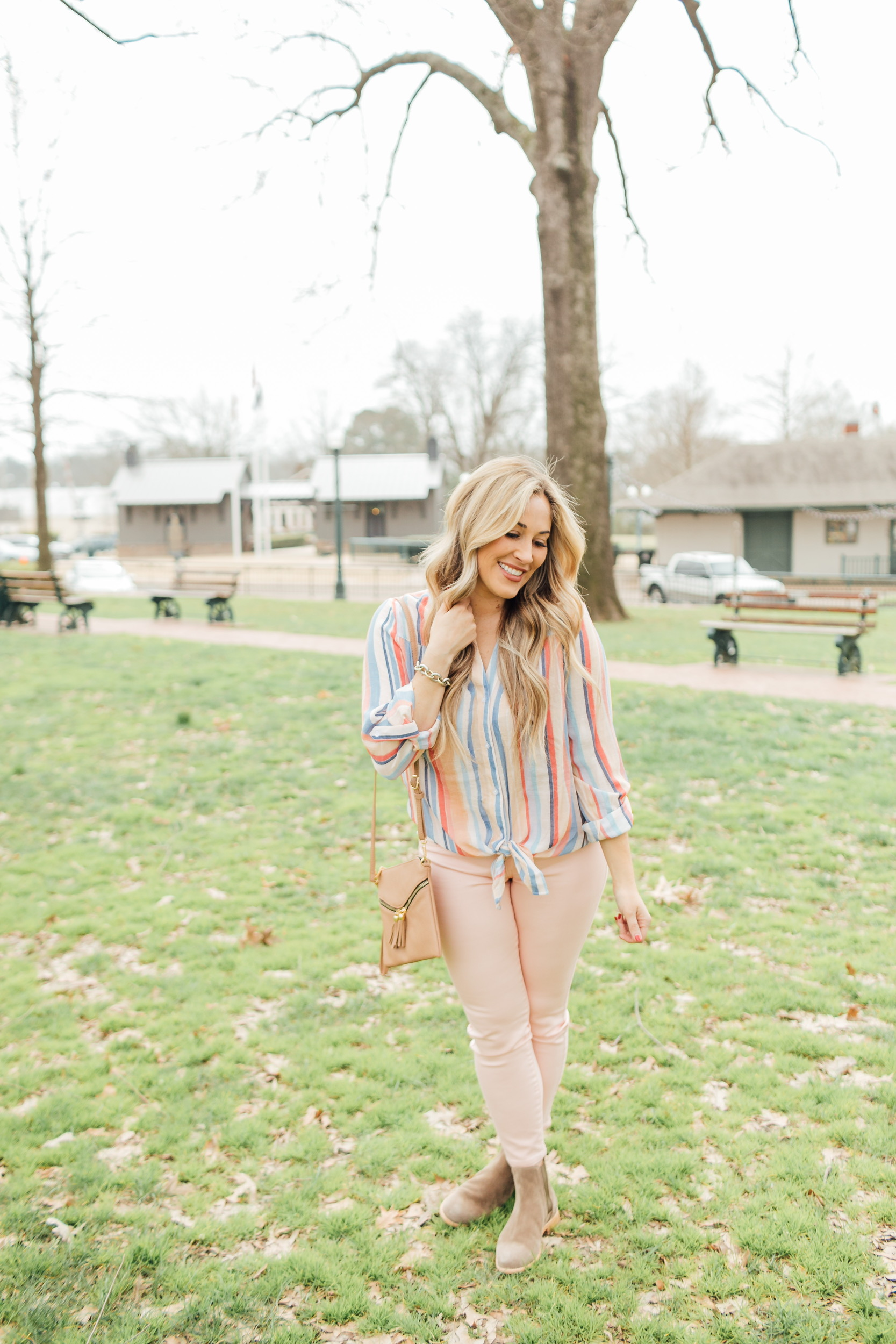 Spring outfit from Gordmans styled by top US fashion blog, Walking in Memphis in High Heels: image of a woman wearing peach jeans, striped button down shirt, and a crossbody bag