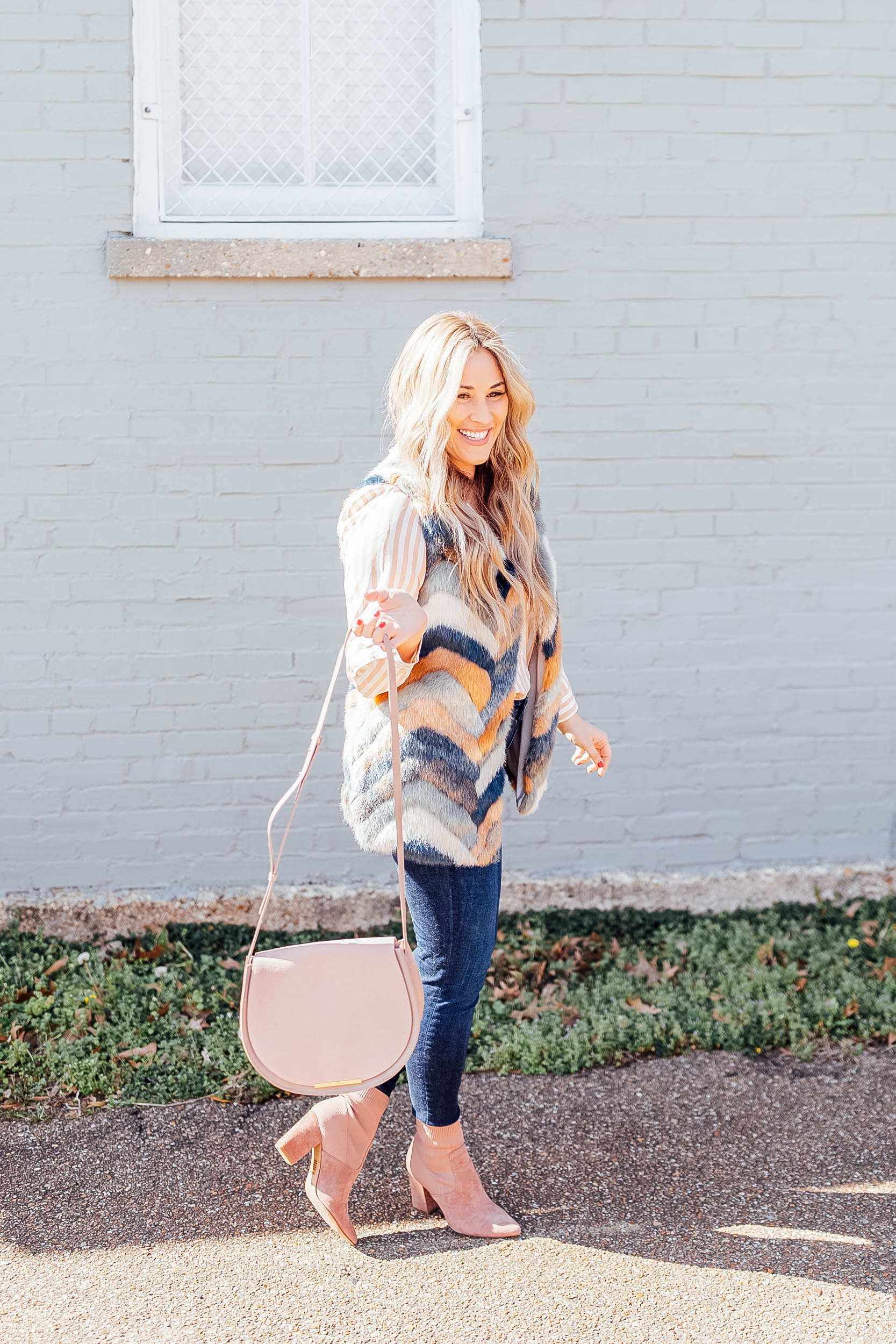 Top US fashion blog, Walking in Memphis in High Heels features their tips for mixing prints: image of a woman wearing a Pink Lily faux fur vest, a Cuyana silk cami, KUT from the Kloth skinny ankle jeans, Steve Madden suede booties and a Cuyana bag
