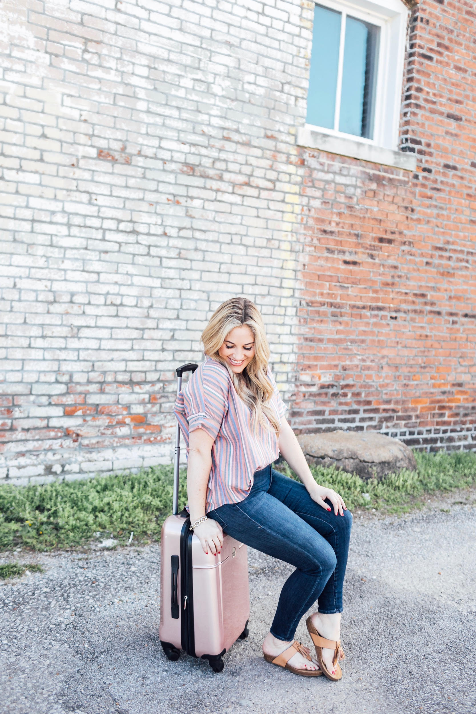 Spring Trip Packing List featured by top US travel and fashion blog, Walking in Memphis in High Heels: image of a woman with a Delsey spinner carry one suitcase