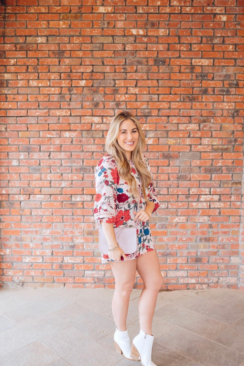 Cute LOFT rompers featured by top US fashion blog, Walking in Memphis in High Heels: image of a woman wearing a floral LOFT romper, Madewell crossbody bag, white Marc Fisher bootie
