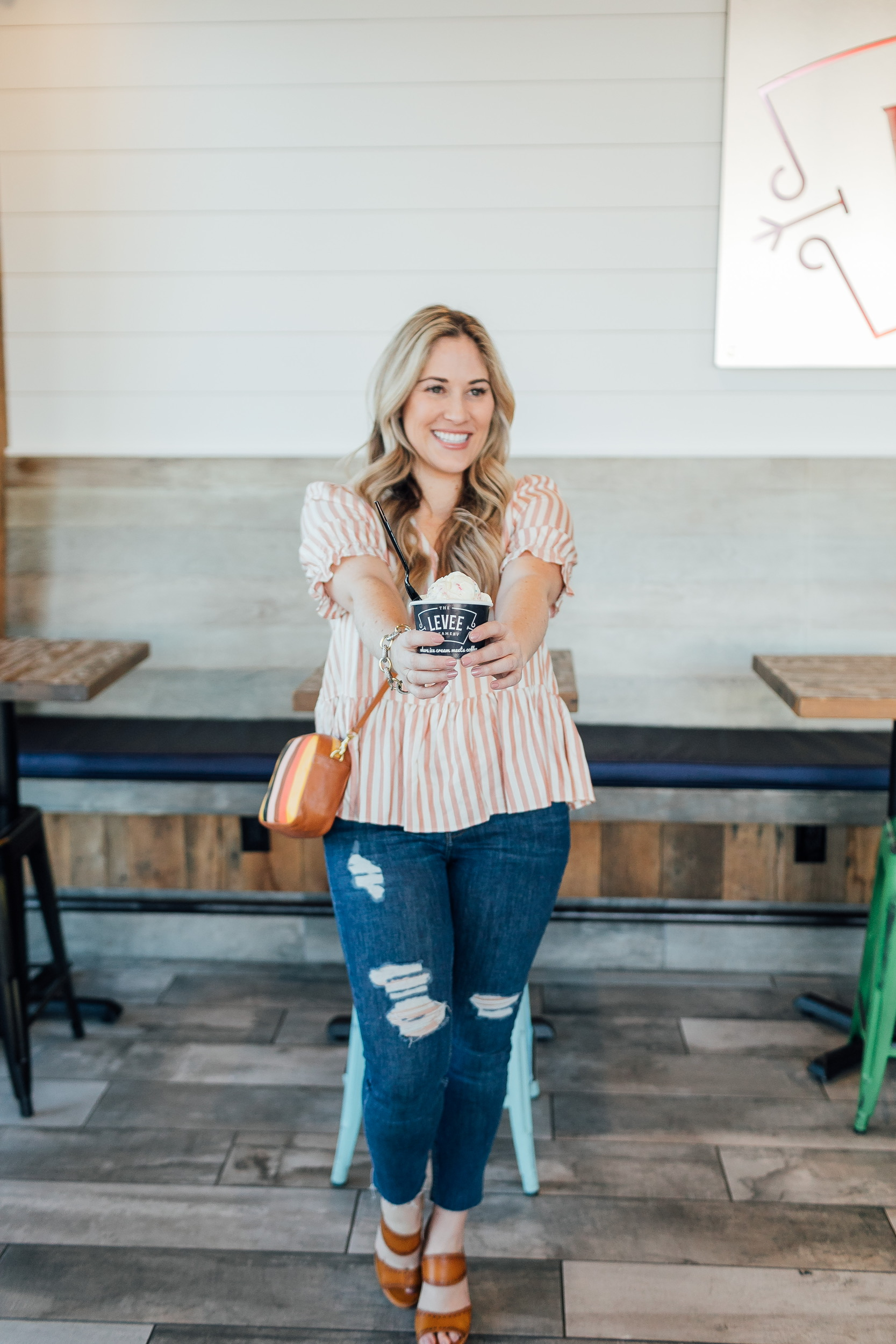 Madewell striped peplum top styled for Spring, featured by top US fashion blog, Walking in Memphis in High Heels: image of a woman wearing a Madewell top, Free People skinny jeans, Zappos sandals, and a Steve Madden crossbody bag.