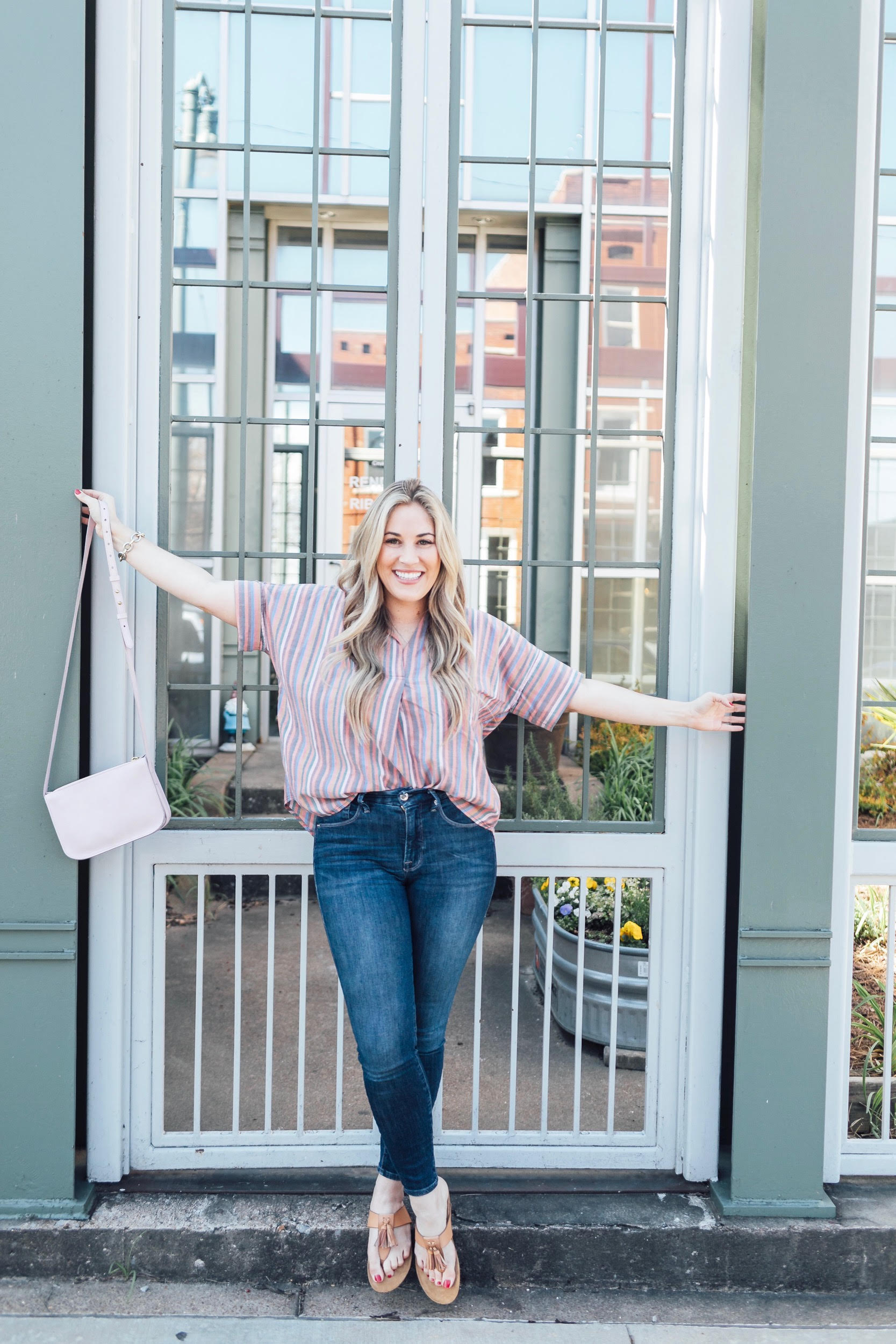 Comfortiva Gella tassel sandals style by top US fashion blog, Walking in Memphis in High Heels: image of a woman wearing a Madewell striped shirt, Good American skinny jeans, a Madewell crossbody bag, and Comfortiva Gella tassel sandals
