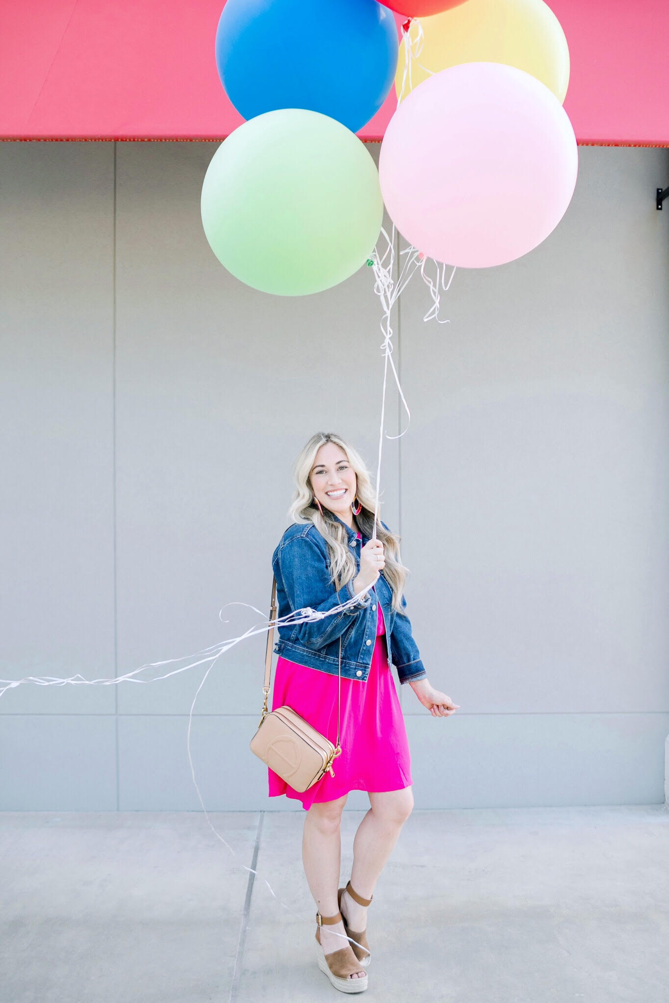 Cute summer dresses featured by top US fashion blog, Walking in Memphis in High Heels: image of a woman wearing a Gordmans pink halter neck dress, Everlane cropped denim jacket, Marc Fisher wedge sandals, and Baublebar raffia statement earrings.