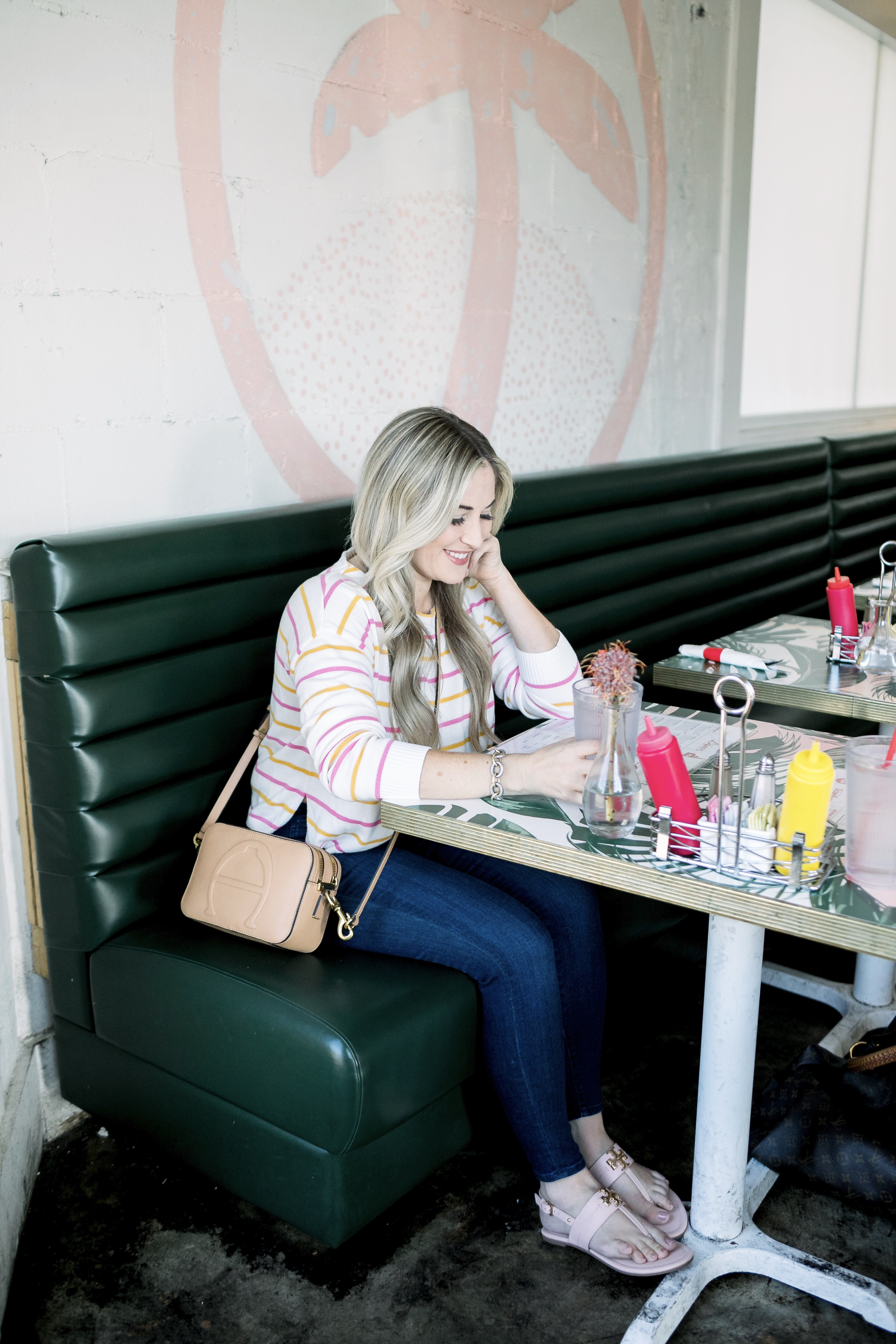 Cute summer to fall casual look styled by top US fashion blog, Walking in Memphis in High Heels: image of a woman wearing a Pink Lily Boutique striped sweater, Good American high waisted skinny jeans, and Tory Burch sandals.