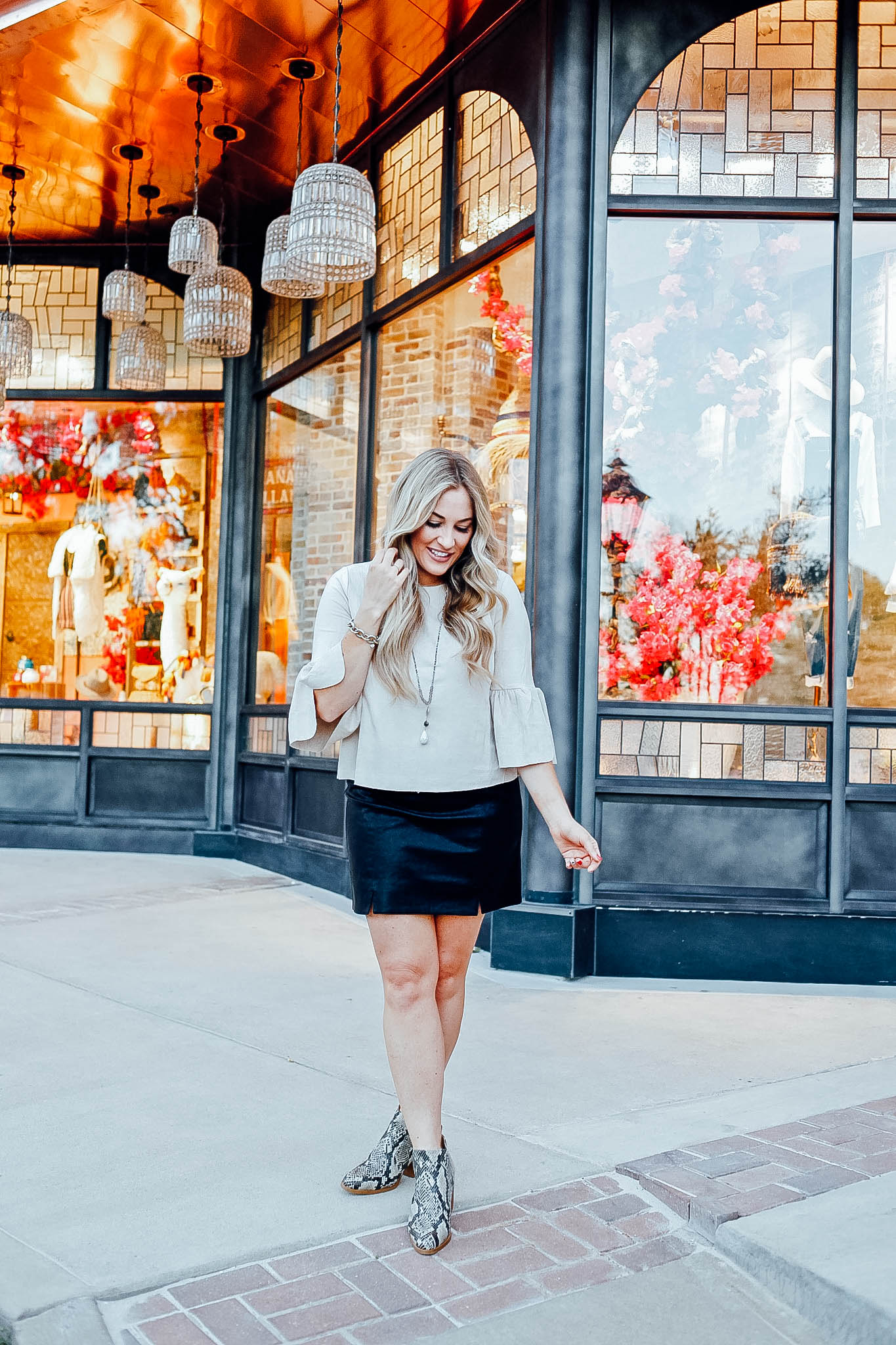 Fall Fashion Essentials featured by top US fashion blog, Walking in Memphis in High Heels: image of a woman wearing snakeskin leather booties, faux leather mini skirt, suede bell sleeve top from Altar'd Sata.