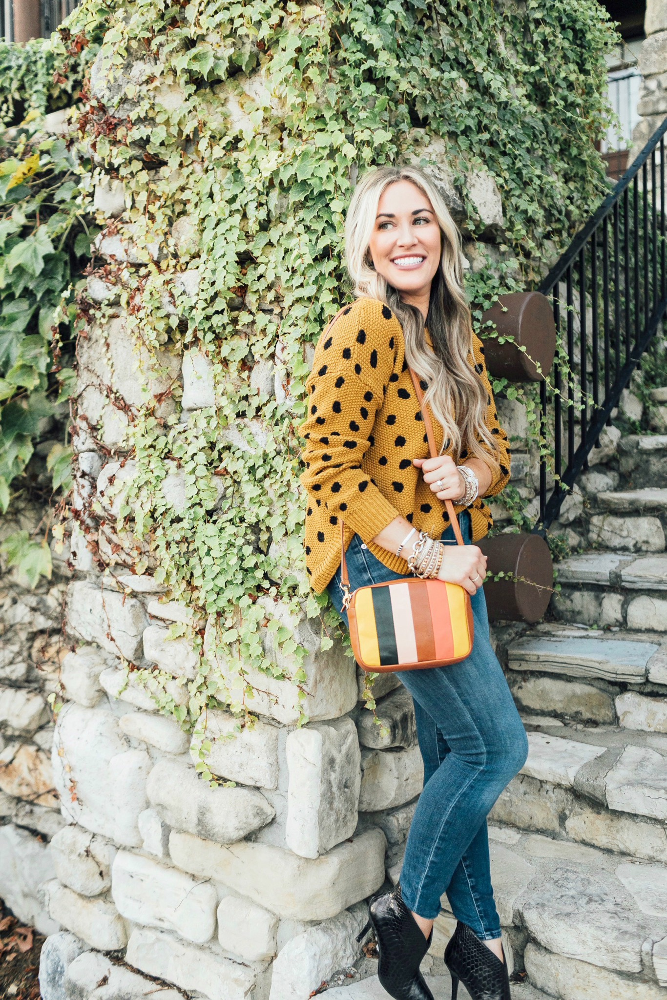 Fall trend colors featured by top US fashion blog, Walking in Memphis in High Heels: image of a woman wearing Good American skinny jeans, Vince Camuto booties, Clare V. Striped crossbody bags, and  Victoria Emerson stackable bracelets.