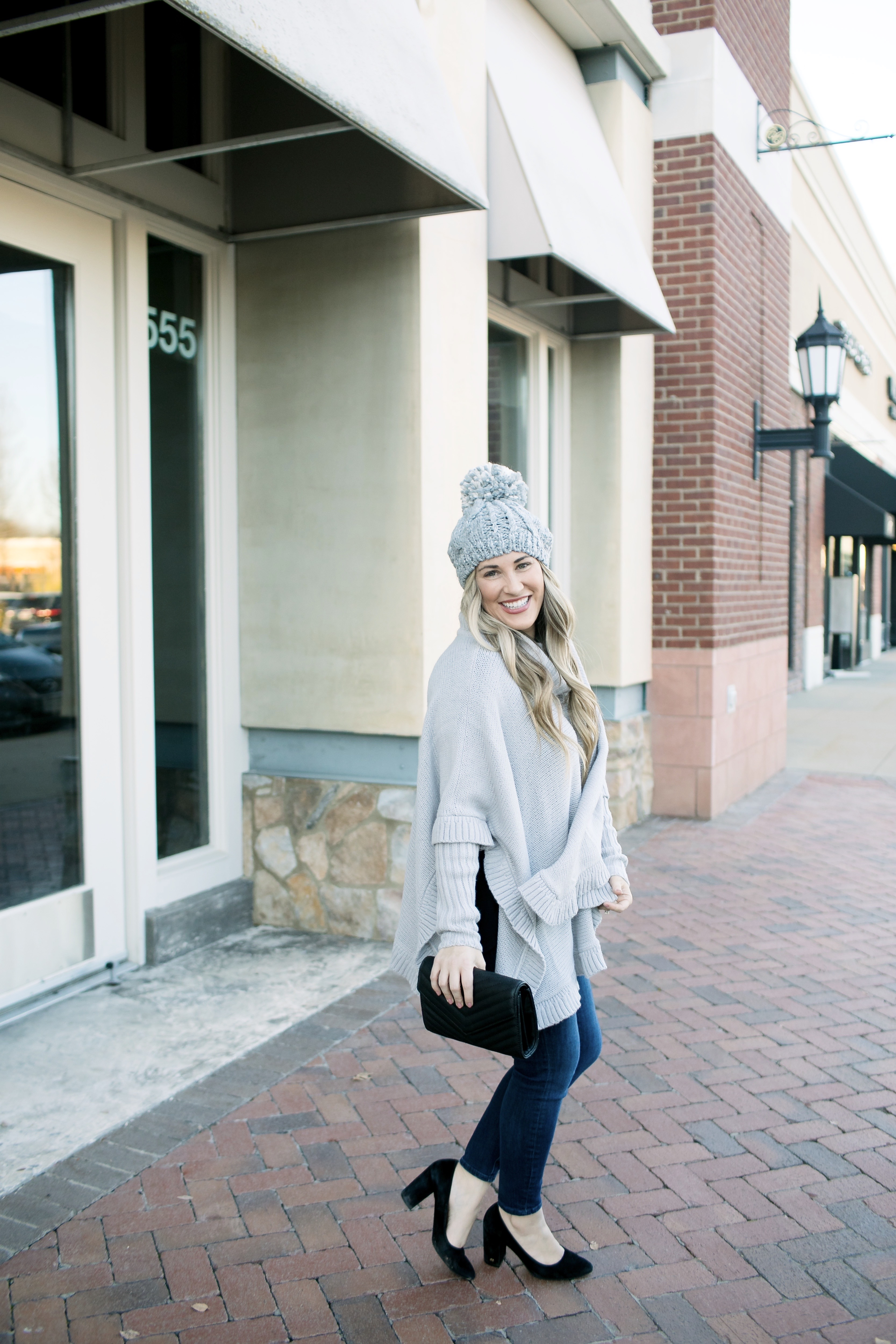 Last Minute Stocking Stuffers from Francesca's at Carriage Crossing featured by top US fashion blog, Walking in Memphis in High Heels: image of a woman wearing Francesca's straight jeans, a quilted clutch, a beanie hat and and a poncho.