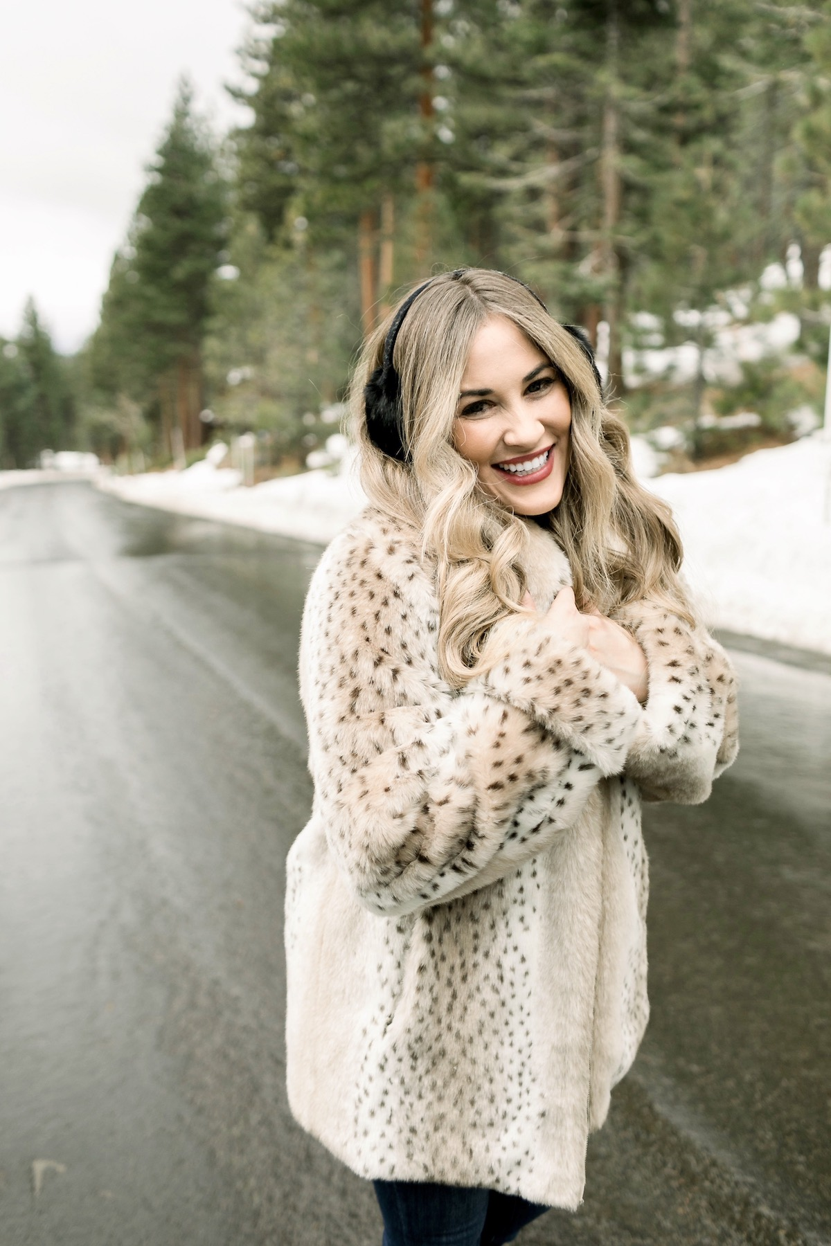 Winter Essentials featured by top Memphis fashion blog, Walking in Memphis in High Heels: image of a woman wearing an ARIAT top, Dennis Basso leopard faux fur coat, Good American high rise skinny jeans, Enzo Angiolini booties, and Surell earmuffs.