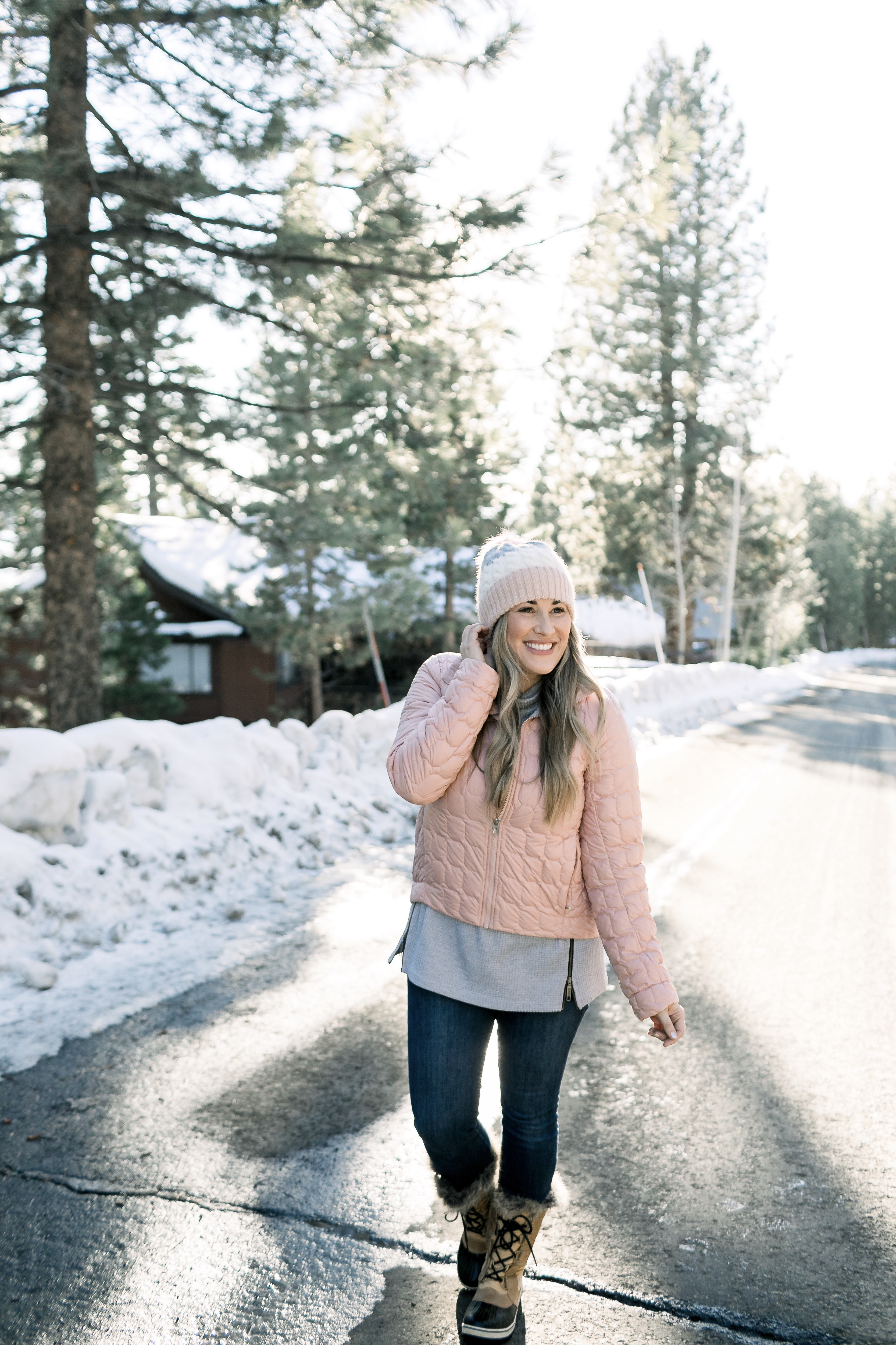 How to Wear Pastels in the Winter, fashion tips featured by top Memphis blog, Walking in Memphis in High Heels: image of a woman wearing a light pink The North Face crop jacket, ASOS blush pom beanie, Sorel blush snow boots.