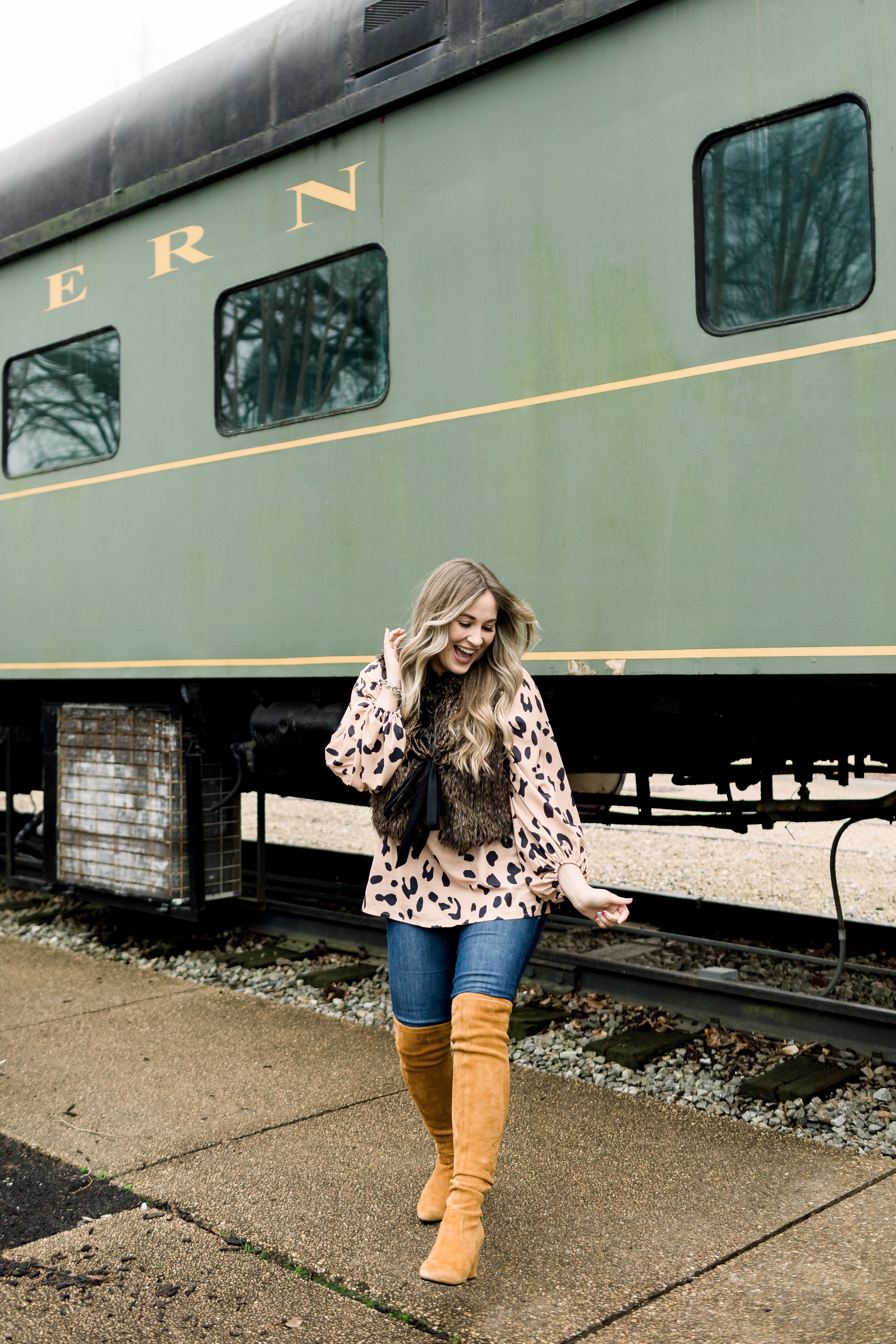 Animal print top styled by top Memphis fashion blog, Walking in Memphis in High Heels: image of a woman wearing an Amazon Chiffon animal print top, LOFT faux fur vest, Good American jeans and Goodnight Macaroon over the knees suede boots.