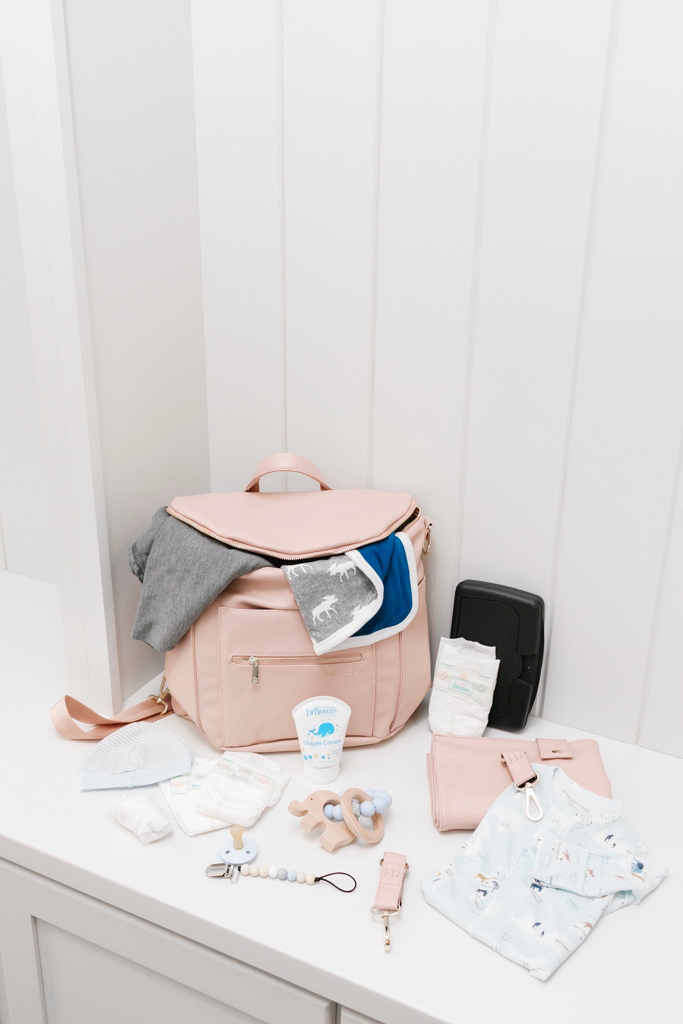 Diaper Bag Essentials featured by top Memphis mommy blogger, Walking in Memphis in High Heels: image of a woman wearing a Fawn Design blush diaper bag.
