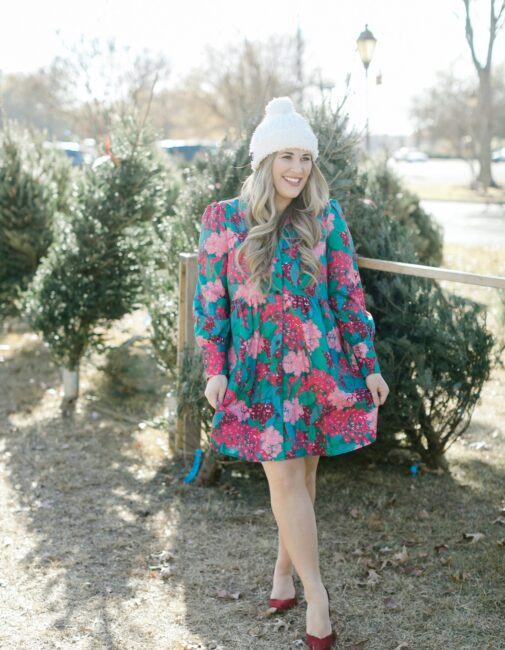 Winter floral look styled by top Memphis fashion blogger, Walking in Memphis in High Heels: image of a woman wearing a Tuckernuck floral shirt dress, Vince Camuto Selindra pumps and MUK LUKS pom hat.