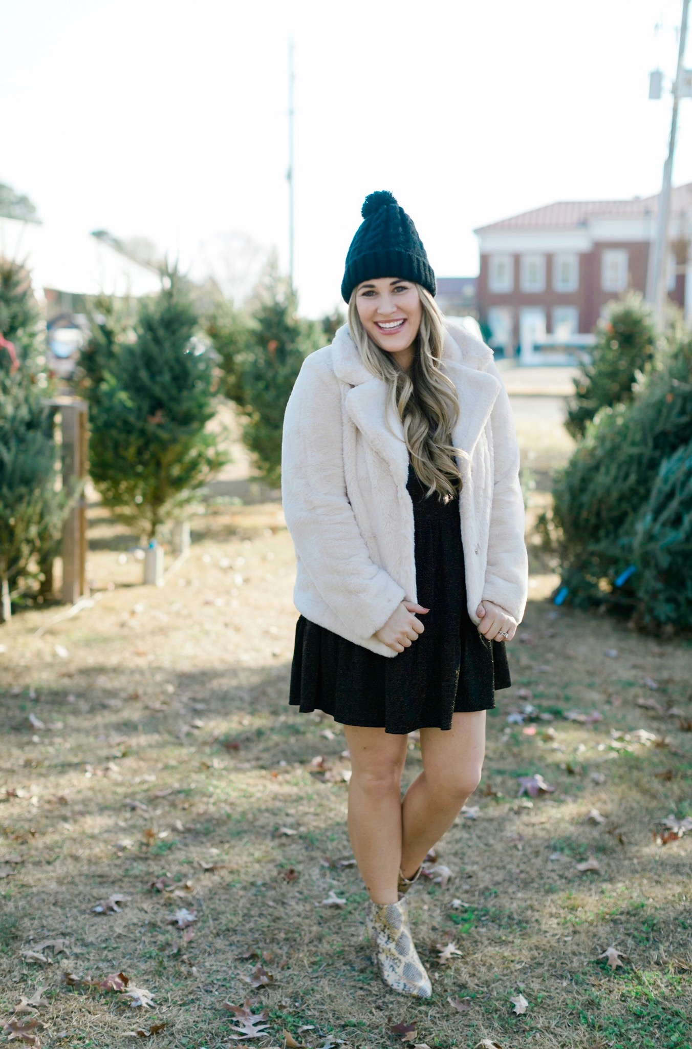 New Years Eve Outfits featured by top Memphis fashion blogger, Walking in Memphis in High Heels: Image of a woman wearing an RBBK holiday dress, Express faux fur coat, Tasha pom beanie, and Red Dress ankle booties