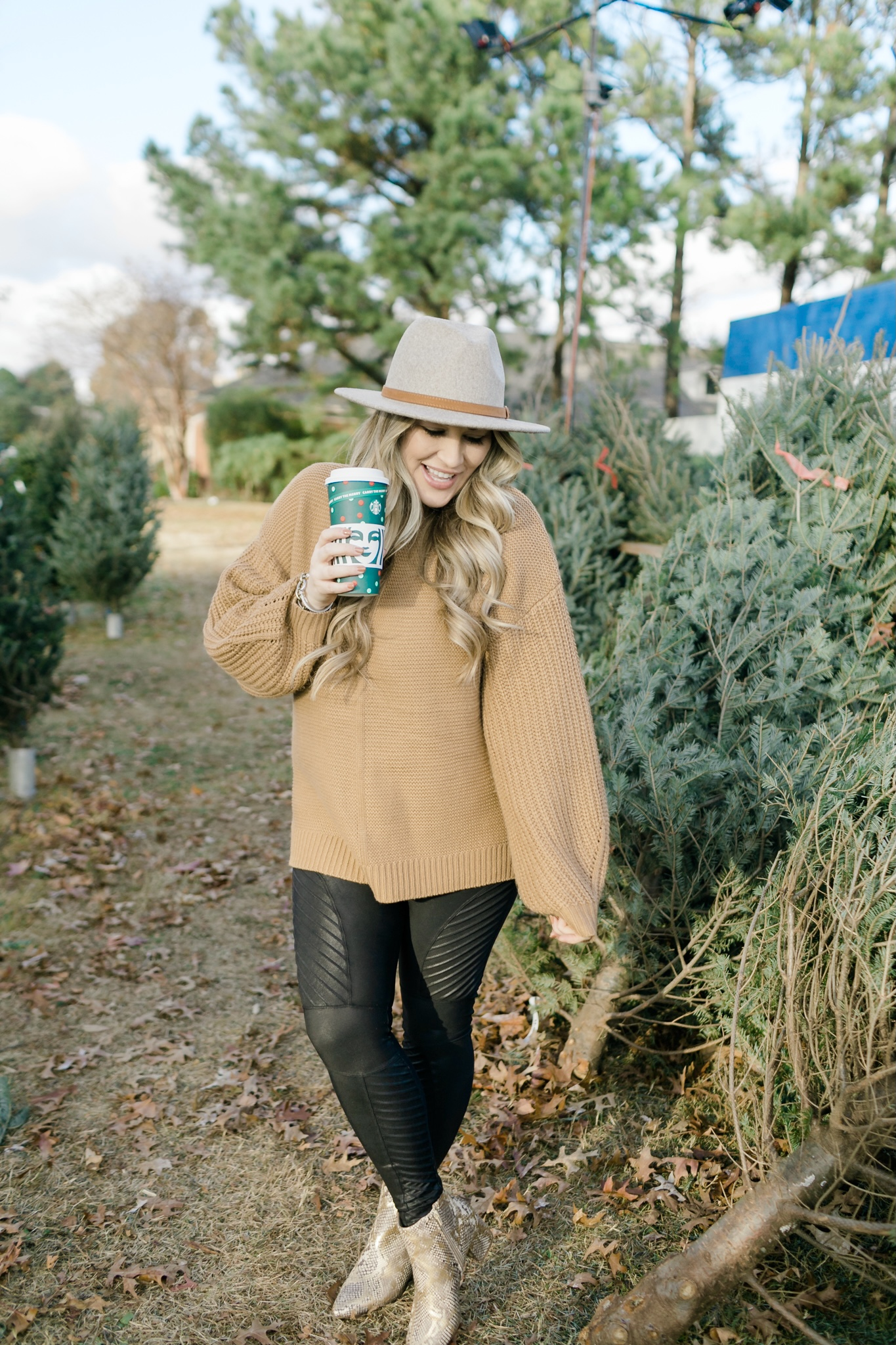 How to Wear a Sweater with Leggings, tips featured by top Memphis fashion blogger, Walking in Memphis in High Heels: image of a woman wearing Red Dress Camel Sweater and SPANX faux leather motto leggings