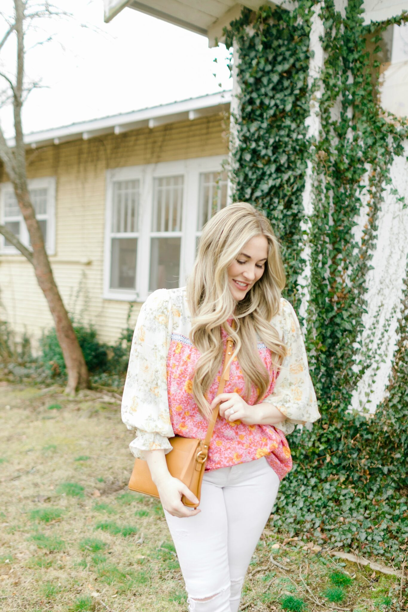 Cute Spring Outfit styled by top Memphis fashion blogger, Walking in Memphis in High Heels: image of a woman wearing a Red Dress Boutique floral top, Express high waisted skinny white jeans, and Gigi New York crossbody bag.
