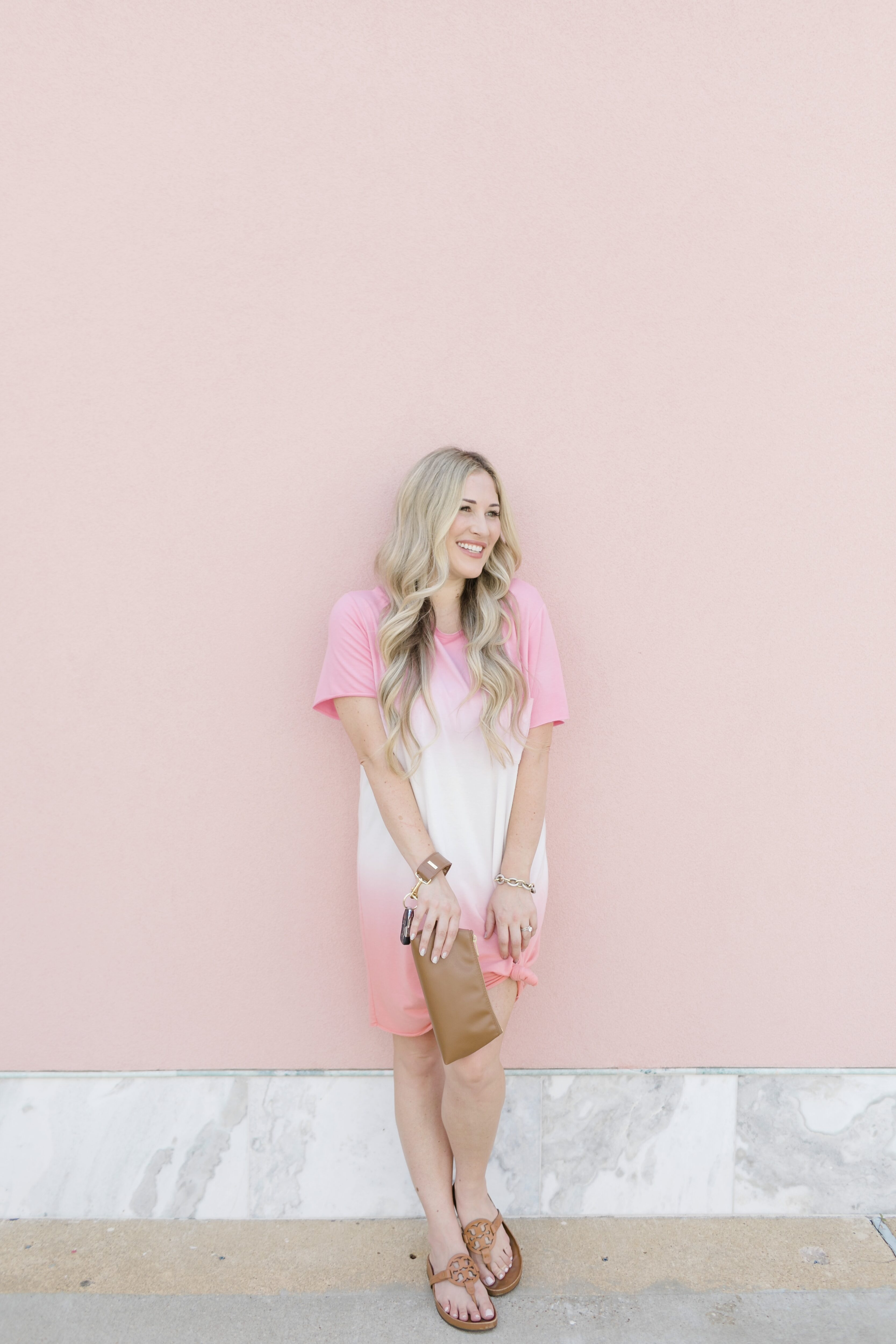 Late summer casual outfit featured by top US mommy fashion blogger, Walking in Memphis in High Heels: image of a woman wearing a Mud Pie pink tie dye dress, Tory Burch sandals and a Keyper wristlet.